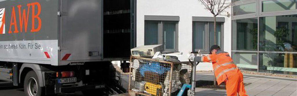 Müllwerker in orangenen Westen schieben Elektroschrott in einen Lastwagen